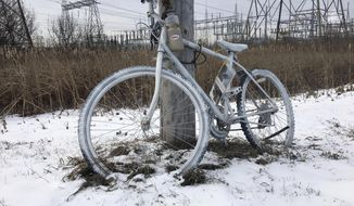 "A ghost bike sits at the intersection of Maxwell Avenue and Red Rock Road in Newport, Minn., near the entrance ramp to westbound Interstate 494, on Jan. 11, 2018. This was the site where a truck hit bicyclist Peter Morey. After Morey died in May 2017, his brother put up a ghost bike at the intersection, according to Morey's wife, Krista Morey. The bikes are known as ""ghost bikes"" to commemorate casualties of bike accidents.  (Bob Shaw/Pioneer Press via AP)"