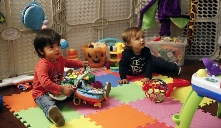 Sixteen-month-old Ethan Dvash-Banks, left, and his twin brother, Aiden, play in the living room of their apartment Tuesday, Jan. 23, 2018, in Los Angeles. The toddler twins share almost everything: the same toys, the same nursery, the clothes and the same parents. Everything but a toothbrush and U.S. citizenship. Ethan became a plaintiff in a federal lawsuit against the U.S. State Department that seeks the same rights his brother has as a citizen. (AP Photo/Jae C. Hong)