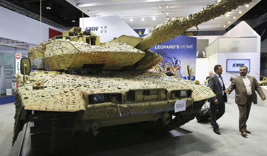 """FILE - In this Feb. 22, 2017 file photo, men walk past a Krauss-Maffei Wegmann Leopard tank with a """"sold"""" sign on it at the International Defense Exhibition and Conference, known by the acronym IDEX, in Abu Dhabi, United Arab Emirates.  Newly released figures on Wednesday, Jan. 24, 2018 show Germany's centrist coalition approved more weapons exports over the past four years, fueling debate over the country's weapons sale policy. (AP Photo/Jon Gambrell,file)"""