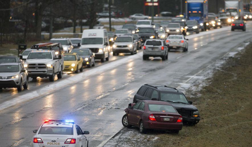 Cars sit on the sidelines of 56th street, where crashes, delays, and slide-offs are common during a slow commute that is compounded by a layer of slick ice that fell overnight, in Indianapolis, Wednesday, Jan. 24, 2018. (Robert Scheer//The Indianapolis Star via AP)