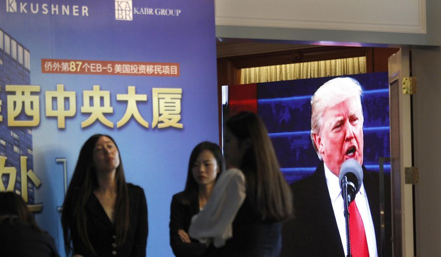 FILE- In this May 7, 2017 file photo, a projector screen shows a footage of U.S. President Donald Trump as workers wait for investors at a reception desk during an event promoting EB-5 investment in a Kushner Companies development, at a hotel in Shanghai, China. The family real estate company once run by Jared Kushner is no longer seeking $150 million from wealthy Chinese for a two-tower residential complex in Jersey City, N.J., after government ethics experts in 2017 blasted the Kushner Cos. for what they said was an attempt to use its ties to the White House to raise the money. (AP Photo, File)
