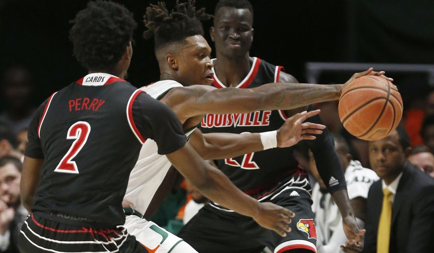 Miami guard Lonnie Walker IV, center, reaches for the ball between Louisville guard Darius Perry (2) and forward Deng Adel (22) during the first half of an NCAA college basketball game Wednesday, Jan. 24, 2018, in Coral Gables, Fla. (AP Photo/Wilfredo Lee)
