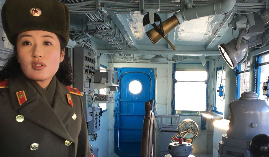 In this Wednesday, Jan. 24, 2018, photo, a North Korean military guide leads a tour of the USS Pueblo in Pyongyang, North Korea. The Pueblo, an American spy ship, was attacked and captured by North Korea 50 years ago this week. The iconic spy ship, on display in Pyongyang, is the only commissioned US Navy ship held by a foreign government. (AP Photo/Eric Talmadge)