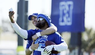NFC quarterback Drew Brees, left,and running back Alvin Kamara, both of the New Orleans Saints, take a selfie during Pro Bowl NFL football practice, Wednesday, Jan. 24, 2018, in Kissimmee, Fla. (AP Photo/Gregory Payan)