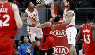 Toronto Raptors' Fred VanVleet, center, shoots between Atlanta Hawks' Kent Bazemore (24) and Tyler Dorsey during the second quarter of an NBA basketball game in Atlanta, Wednesday, Jan. 24, 2018. (AP Photo/David Goldman)