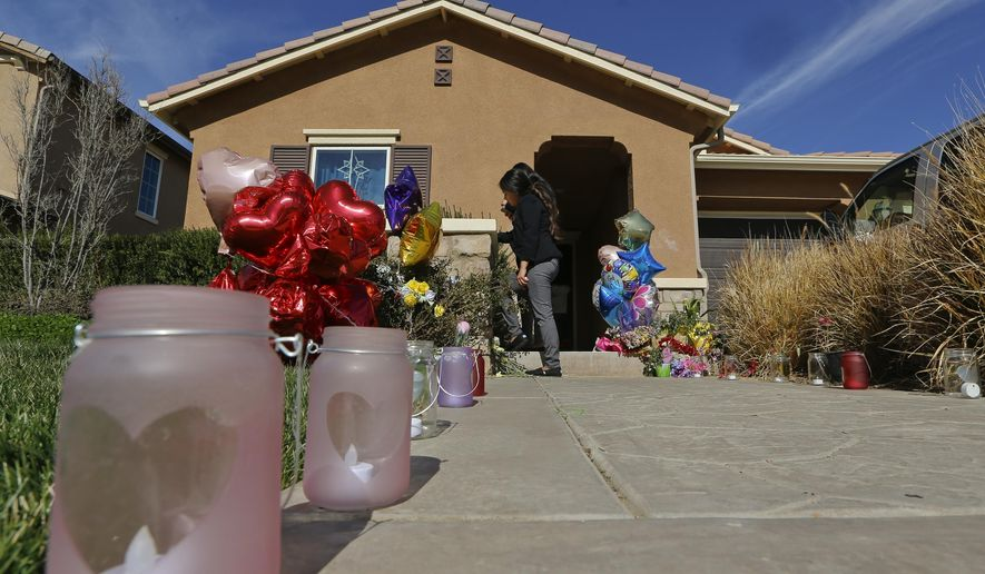 Neighbors write down messages for the Turpin's children on the front door of the home of David and Louise Turpin where police arrested the couple accused of holding 13 children captive in Perris, Calif., Wednesday, Jan. 24, 2018. The Turpin's accused of abusing their 13 children, ranging from 2 to 29, before they were rescued on Jan. 14 from their home in Perris. They have pleaded not guilty to torture and other charges. A judge signed a protective order Wednesday prohibiting the couple from contacting their children, except through attorneys or investigators. (AP Photo/Damian Dovarganes)