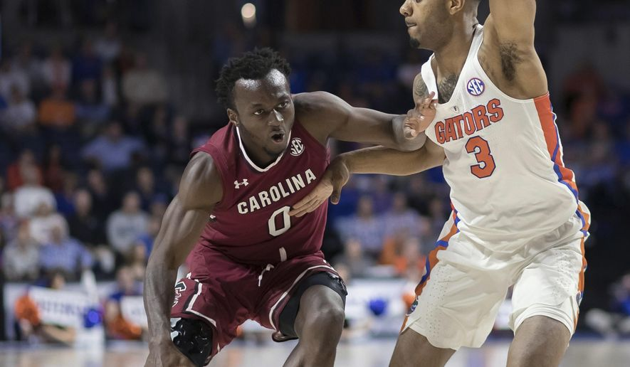 South Carolina guard David Beatty (0) dribbles against the defense by Florida guard Jalen Hudson (3) during the first half of an NCAA college basketball game in Gainesville, Fla., Wednesday, Jan. 24, 2018. (AP Photo/Ron Irby)