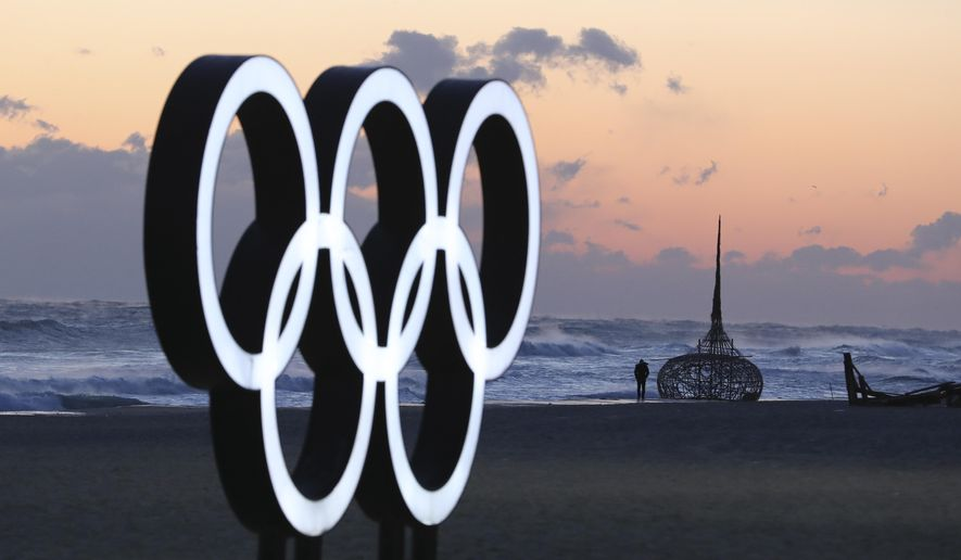 A visitor walks along the beach near the Olympic Rings in Gangneung, South Korea, Wednesday, Jan. 24, 2018. Gangneung is the site of the coastal cluster which will host ice hockey, figure skating, speedskating, short track and curling for the 2018 Olympics. The 2018 Pyeongchang Games will be held from Feb. 9 to 25. (AP Photo/Lee Jin-man)