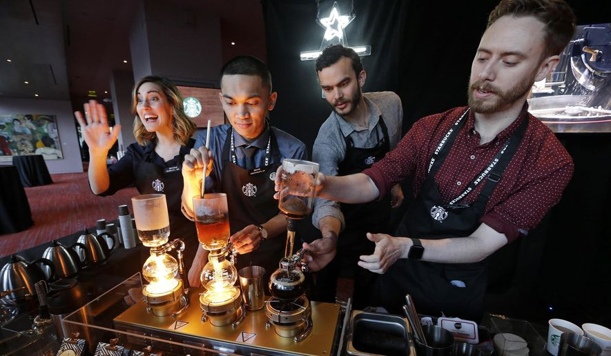 Baristas from Starbucks' specialized coffee shop, Reserve Roastery, demonstrate a siphon brew of individual cups of coffee before the company's annual shareholder meeting in Seattle, March 22, 2017. (AP Photo/Elaine Thompson) ** FILE **