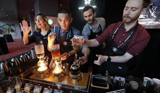 FILE - In this Wednesday, March 22, 2017, file photo, baristas from Starbucks' specialized coffee shop, Reserve Roastery, demonstrate a siphon brew of individual cups of coffee before the company's annual shareholder meeting in Seattle. Starbucks is giving its U.S. workers pay raises and stock bonuses in 2018, citing recent tax reform. The coffee chain is also extending the potential to earn paid sick time off to all employees, and is boosting its parental leave benefits. (AP Photo/Elaine Thompson, File)