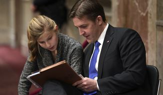 Sen. Ben Sasse, R-Neb., helps his daughter Alexandra Sasse, 14, with her algebra homework while sitting near the audience at the Senate Armed Services Committee hearing on Capitol Hill in Washington, Thursday, Jan. 25, 2018. (AP Photo/Susan Walsh)
