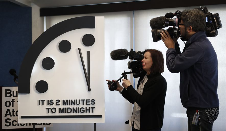 Members of the media film the Doomsday Clock during a news conference at the National Press Club in Washington, Thursday, Jan. 25, 2018, announcing that the Bulletin of the Atomic Scientists has moved the minute hand of the Doomsday Clock to two minutes to midnight. ( AP Photo/Carolyn Kaster)