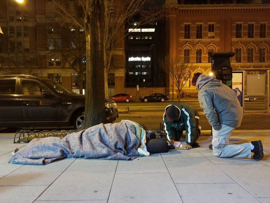 Hector Lugo, right, and Kevin Morton, left, kneel by a bus stop as they survey a homeless man Wednesday night for the annual Point-In-Time census of homelessness in the District. (Julia Airey/The Washington Times). **FILE**