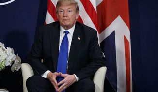 President Donald Trump listens during a meeting with British Prime Minister Theresa May at the World Economic Forum, Thursday, Jan. 25, 2018, in Davos. (AP Photo/Evan Vucci)
