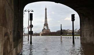 View of the flooded banks of the river Seine in front of the Eiffel tower in Paris, Wednesday, Jan. 24, 2018. The Seine River has overflowed its banks in Paris, prompting authorities to close several roads and cancel boat cruises as water levels rose at least 3.3 meters (nearly 11 feet) above the normal level. (AP Photo/Thibault Camus)
