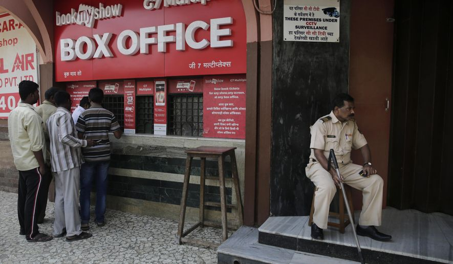 """A policeman guards as people buy tickets at a movie theatre screening Bollywood film """"Padmaavat"""" in Mumbai, India, Thursday, Jan. 25, 2018. The film, based on a 16th century Sufi epic poem, has sparked protests and anger due to allegations of distorting history. (AP Photo/Rafiq Maqbool)"""