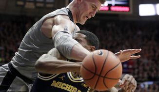 Purdue center Isaac Haas (44) fouls Michigan guard Charles Matthews (1) during the first half of an NCAA college basketball game in West Lafayette, Ind., Thursday, Jan. 25, 2018. (AP Photo/Michael Conroy)
