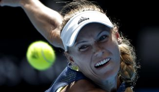 Denmark's Caroline Wozniacki eyes the ball to make a return to Belgium's Elise Mertens during their semifinal at the Australian Open tennis championships in Melbourne, Australia, Thursday, Jan. 25, 2018. (AP Photo/Vincent Thian)