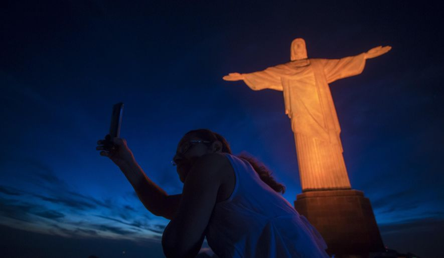 FILE - In this Nov. 25, 2017 file photo, a tourist takes a selfie with the Christ the Redeemer statue illuminated in orange to mark the International Day for the Elimination of Violence against Women, in Rio de Janeiro, Brazil. Starting Thursday, Jan. 25, Brazil is making it easier and cheaper for Americans to apply for a visa following a decline in the number of visitors from the U.S. in recent years. (AP Photo/Bruna Prado, File)