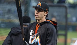 FILE - In this Sept. 25, 2017, file photo, Miami Marlins center fielder Christian Yelich steps out of the cage during batting practice before the team's baseball game against the Colorado Rockies in Denver. The Marlins sent Yelich to the Milwaukee Brewers for four prospects on Thursday, Jan. 25, 2018. (AP Photo/David Zalubowski, File) **FILE**