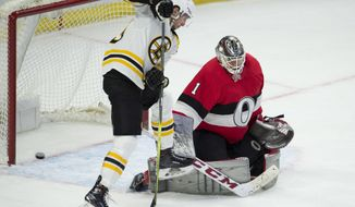 Boston Bruins center Tim Schaller (59) tries to tip the puck into the net behind Ottawa Senators goaltender Mike Condon (1) during the second period of an NHL hockey game Thursday, Jan. 25, 2018, in Ottawa, Ontario. (Adrian Wyld/The Canadian Press via AP)