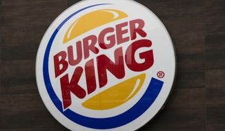 This Oct. 21, 2016, file photo shows a Burger King restaurant logo in Philadelphia. Burger King has delivered its own hot take on a regulatory showdown that has enflamed the U.S., with a flame-grilled Whopper. The new ad has become a sensation, with more than a million views and counting on YouTube. In the ad, customers are told they will be charged different prices for a Whopper, depending on how fast they want it. (AP Photo/Matt Rourke, File)