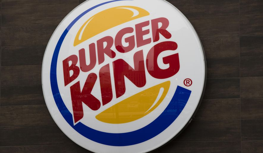 FILE - This Oct. 21, 2016, file photo shows a Burger King restaurant logo in Philadelphia. Burger King has delivered its own hot take on a regulatory showdown that has enflamed the U.S., with a flame-grilled Whopper. The new ad has become a sensation, with more than a million views and counting on YouTube. In the ad, customers are told they will be charged different prices for a Whopper, depending on how fast they want it. (AP Photo/Matt Rourke, File)