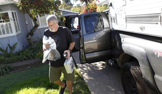 Eric Arneson unloads his truck after returning to his home in Montecito, Calif., Thursday, Jan. 25, 2018. Residents are trickling back to the California coastal town that was devastated two weeks ago by mudslides that killed at least 21 people and destroyed more than a hundred homes. (AP Photo/Daniel Dreifuss)