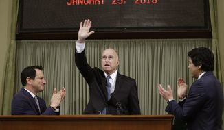California Gov. Jerry Brown waves as he receives applause from Assembly Speaker Anthony Rendon, D-Lakewood, left, and Senate President Pro Tem Kevin de Leon, of Los Angeles before giving his annual State of the State speech before a joint session of the Legislature, Thursday, Jan. 25, 2018, in Sacramento, Calif. Brown delivered his 16th and final address as governor, having served two terms starting in 1975 and returning for two more in 2011. (AP Photo/Rich Pedroncelli)