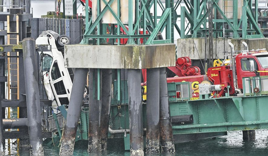 A tow truck lifts a white Jeep Cherokee vehicle out of the water at the Washington State Ferries terminal, Thursday, Jan. 25, 2018, in Anacortes, Wash. Authorities say a 30-year-old woman from Everett died after she drove her Jeep Cherokee through a barrier and off a dock at the Washington State Ferries terminal at Anacortes. (Scott Terrell/Skagit Valley Herald via AP)