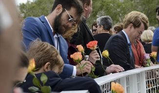 Tal Ramon, left with sunglasses, son of space shuttle Columbia astronaut Ilan Ramon, and other friends and family of fallen astronauts place flowers in the fence at the Space Mirror Memorial at Kennedy Space Center Visitor Complex Thursday, Jan 25, 2018, during Kennedy Space Center's annual day of remembrance. The annual event honors those who perished in the space program. (Craig Bailey /Florida Today via AP)