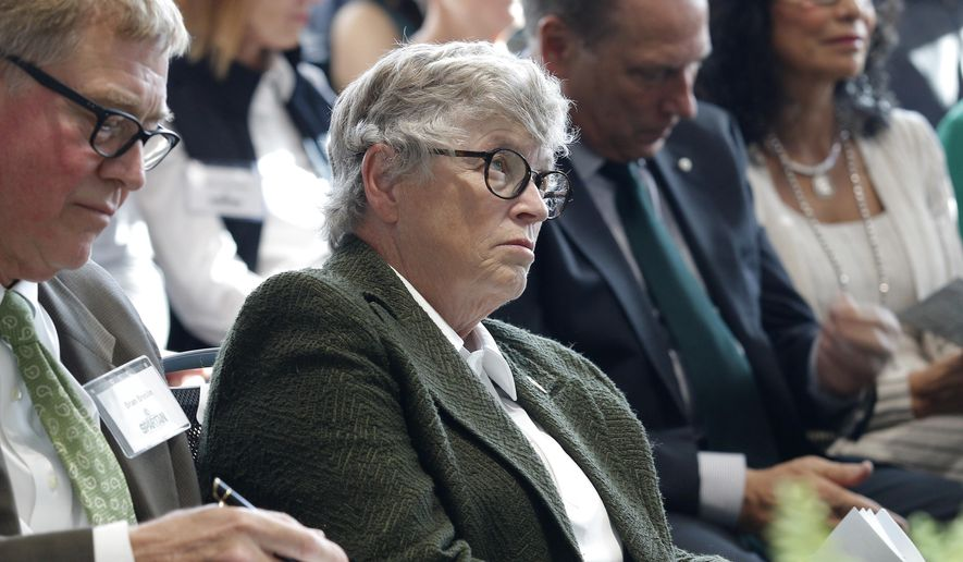 In this Oct. 20, 2017, photo, Michigan State University President Lou Anna Simon listens during the dedication ceremony for the Gilbert Pavilion and Tom Izzo Hall of History inside Michigan State's Breslin Student Events Center in East Lansing, Mich. At left is Brian Breslin, of the university's Board of Trustees. Simon submitted her resignation Wednesday amid an outcry over the school's handling of allegations against Larry Nassar. (AP Photo/Al Goldis)