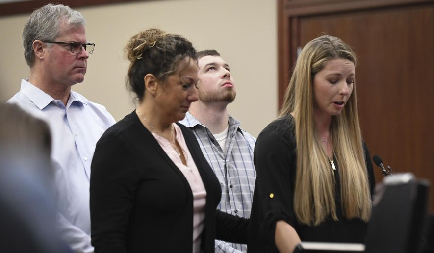 FILE- In this Jan. 22, 2018, file photo, Whitney Mergens speaks during the fifth day of victim impact statements against Larry Nassar in Ingham County Circuit Court. Mergens' parents and boyfriend stand at her side. (Matthew Dae Smith/Lansing State Journal via AP, File)