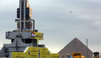 "A drone hovers as a statue of Egyptian Pharaoh Ramses II is relocated at the Grand Egyptian Museum near the great Pyramids, in Cairo, Egypt, Thursday, Jan. 25, 2018. The museum is scheduled to open later this year. Arabic at top reads, ""long live Egypt."" (AP Photo/Amr Nabil)"