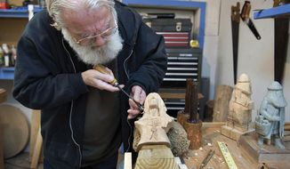 "In this Jan. 12, 2018 photo, Viet Nam veteran and multimedia artist Charles Payne works on a  wood carving in his home in Sterling, Ill. It's the latter two aspects of his life, the artistry and the spirituality, that have helped Payne cope the past 50 years with the former. ""I wasn't wounded by bullets, but by Agent Orange,"" Payne said. ""And then here I am. Still plugging away. My eyes are deteriorating, but my spirit isn't."" The Vietnam veteran continues to work despite having health concerns from Agent Orange. (Alex T. Paschal/The Daily Gazette via AP)"