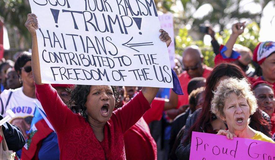 FILE- This Jan. 15, 2018, file photo shows Haitian community supporters in West Palm Beach, Fla., to protest recent remarks made by President Donald Trump about Haiti. The NAACP has sued the U.S. Department of Homeland Security. The organization says Trump's disparaging comments about immigrants and their home countries is evidence of racial discrimination that has influenced his administration's decision to end protections for roughly 60,000 Haitians. (Damon Higgins/Palm Beach Post via AP, File)