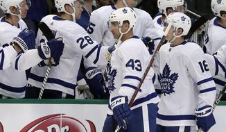 Toronto Maple Leafs center Nazem Kadri (43) and Mitchell Marner (16) are congratulated by the bench after Kadri scored a goal against the Dallas Stars in the first period of an NHL hockey game Thursday, Jan. 25, 2018, in Dallas. (AP Photo/Tony Gutierrez)