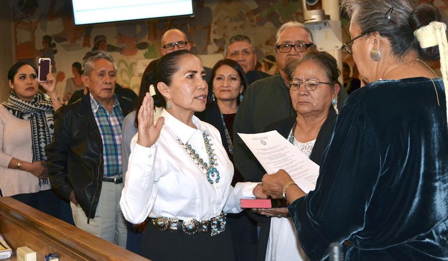 """In this Wednesday, Jan. 24, 2018 photo provided by the Navajo Nation Office of the Speaker, JoAnn """"Joey"""" Jayne, center, is sworn in as the new chief justice of the Navajo Nation Supreme Court, in Window Rock, Ariz. The Navajo Nation Council confirmed Jayne's appointment, and she'll be in probationary status for two years. (Jolene Holgate/Navajo Nation Office of the Speaker via AP)"""