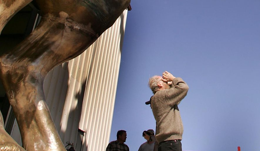 """FILE - In this April 5, 2006 file photo, artist John Sherrill Houser examines the underside of his statue """"The Equestrian"""", at the Eagle Bronze foundry in Lander, Wyo. Houser, a sculptor who created a statue depicting conquistador Don Juan de Onate in El Paso, Texas, that divided residents along ethnic and social class lines, has died. He was 82. (Dan Cepeda/Casper Star-Tribune via AP, File)"""