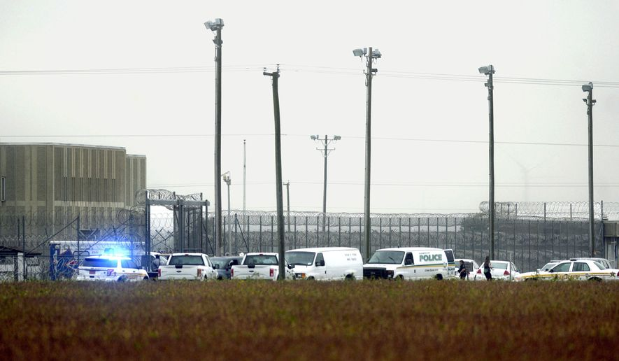 FILE- In this Oct. 12, 2017, file photo, police vehicles are seen outside Pasquotank Correctional Institution in Elizabeth City, N.C. The National Institute of Corrections released a security assessment Thursday, Jan. 25, 2018, of the prison, which said that understaffing was so bad at the prison where four employees were killed during the deadliest breakout attempt in state history that workers cut corners in ways that created opportunities for mayhem. (Thomas J. Turney /The Daily Advance via AP, File)