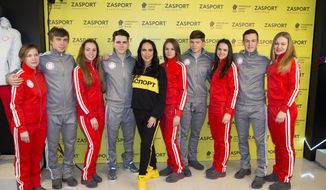 """Russian speed skaters and pose for a photo with Russian outfit company Zasport designer Anastasia Zadorina, center, pose for a photo in the red-and-white and grey-and-white tracksuits, as well as grey coats are modified from the original designs drawn up for Team Russia as potential Olympians. in Moscow, Russia, Monday, Jan. 22, 2018. As a punishment in fallout from the Sochi scandal, Russia has been denied using its flag and badges which are replaced with IOC-approved symbols. Instead of the Russian Olympic Committee logo, there's now a white circle on the chest with the red inscription """"Olympic Athlete from Russia."""" (AP Photo/Alexander Zemlianichenko)"""
