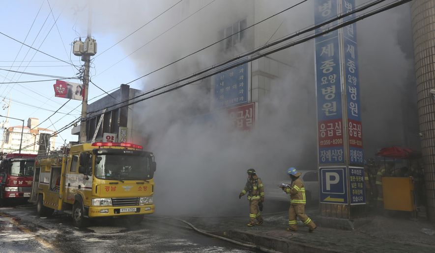 Firefighters work as smoke billows from a hospital in Miryang, South Korea, Friday, Jan. 26, 2018. More than a dozen people were died in the hospital fire, according to a fire official. (Kim Dong-mi/Yonhap via AP)