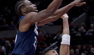 Minnesota Timberwolves forward Andrew Wiggins, left, shoots over Portland Trail Blazers guard Evan Turner during the first half of an NBA basketball game in Portland, Ore., Wednesday, Jan. 24, 2018. (AP Photo/Craig Mitchelldyer)