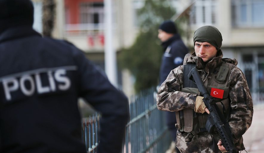 A Turkish special police officer patrols a mosque during the funeral procession for two victims killed on a rocket attack Wednesday night, in the town of Kilis, Turkey, near the border with Syria, Thursday, Jan. 25, 2018. Two rockets fired from inside Syria hit the mosque during evening prayers and a house wounding at least 13 people. It was the latest in a series of rocket attacks against the Turkish border since Ankara launched a military offensive into Afrin to clear it of Syrian Kurdish militiamen whom it considers to be linked with Turkey's own Kurdish insurgents. (AP Photo/Lefteris Pitarakis)