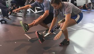 In this image 2015 provided by Jessica Wise, David Wise, left, and his sister Christy workout in San Marcos, Texas. When the doctor told Christy she would never fly a plane again, her goal was set. The Air Force pilot who lost her leg above the knee in a boating accident set about proving him wrong. Hers is a story of determination, perseverance and also about bringing an already tight-knit family even closer. Her twin sister, Jessica, is a surgeon and her brother, David, is an Olympic gold-medal freeskier. Their work is about giving second chances to amputees in third-world countries. (Courtesy Jessica Wise via AP)