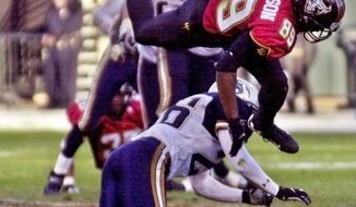 FILE - In this Feb. 4, 2001, file photo, San Francisco Demons wide receiver Brian Roberson jumps over Los Angeles Xtreme cornerback Dell McGee duringthe fourth quarter of an XFL football fam in San Francisco. The XFL is set for a surprising second life, WWE leader Vince McMahon announced Thursday, Jan. 25, 2018. McMahon said the XFL would return in 2020 but offered few other details about the late winter/early spring football league. (AP Photo/Paul Sakuma, FIle)