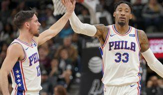 Philadelphia 76ers' T.J. McConnell, left, and Robert Covington celebrate a basket during the first half of the team's NBA basketball game against the San Antonio Spurs, Friday, Jan. 26, 2018, in San Antonio. (AP Photo/Darren Abate)