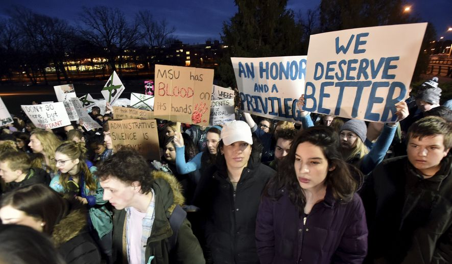 "Demonstrators gather at ""The Rock"" on Michigan State University's East Lansing, Mich., campus to support victims of disgraced former sports doctor Larry Nassar and call for more changes in leadership at the university. (Dale G. Young/Detroit News via AP)"