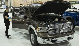 A worker cleans a Dodge Ram 1500 during a press preview of the Philadelphia Auto Show at the Pennsylvania Convention Center in Philadelphia, Friday, Jan. 26, 2018. The event is scheduled to run from Jan. 27 to Feb. 4. (AP Photo/Matt Rourke)
