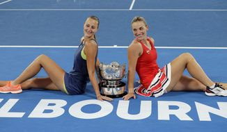 Hungary's Timea Babos, right, and partner France's Kristina Mladenovic pose for a photo with their trophy after they defeated Russia's Ekaterina Makarova and Elena Vesnina in the women's doubles final at the Australian Open tennis championships in Melbourne, Australia, Friday, Jan. 26, 2018. (AP Photo/Dita Alangkara)